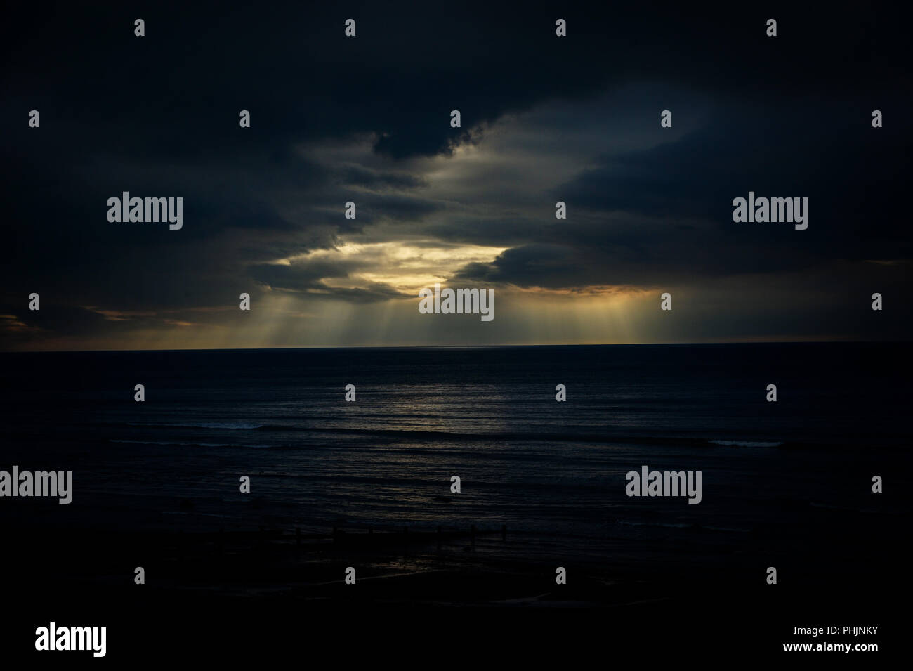 sun rays over cardigan bay from Aberaeron - Stock Image