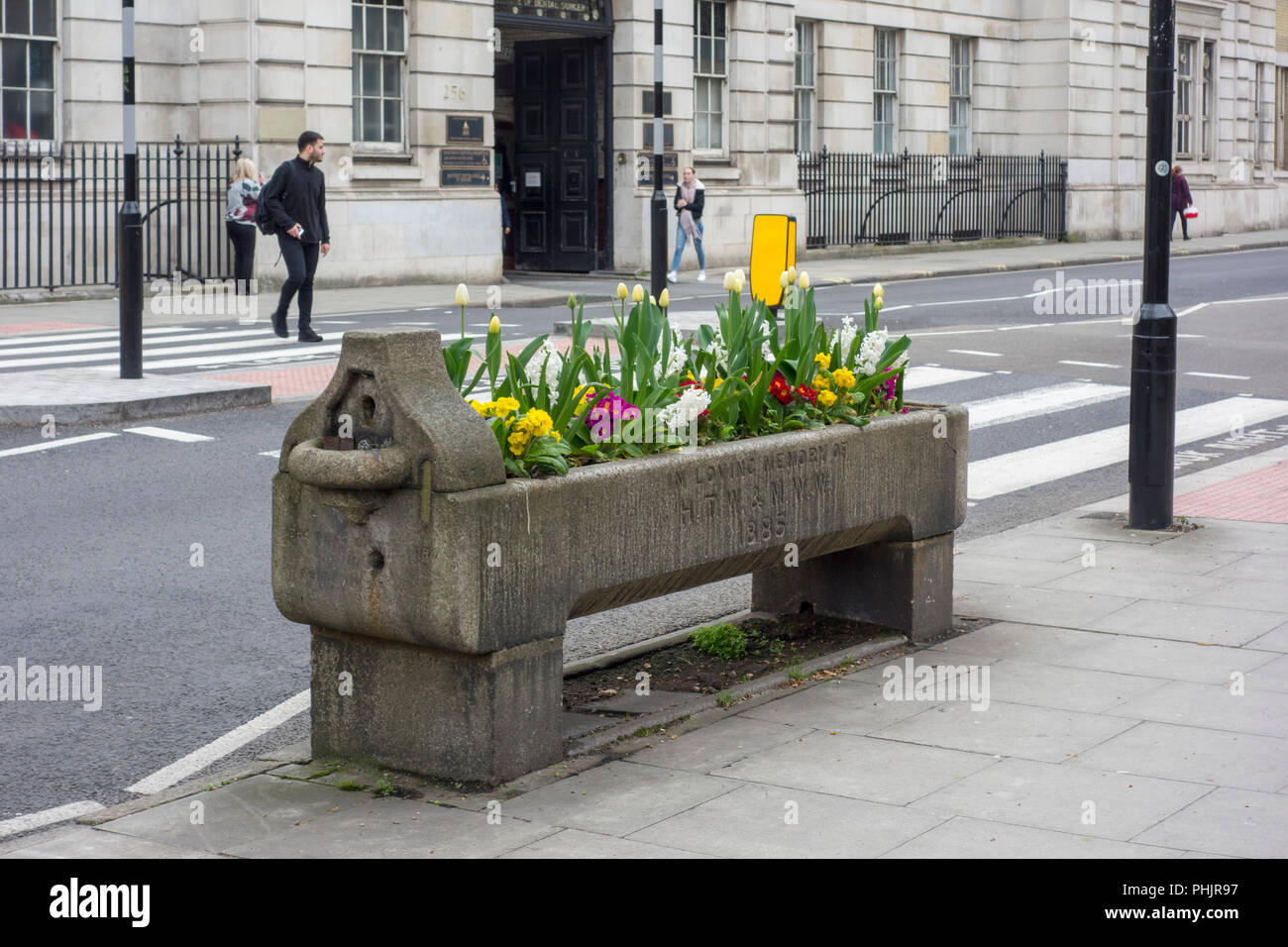 Historic drinking trough planted with flowers, Metropolitan Drinking Fountain and Cattle Trough Association, City of London, UK - Stock Image