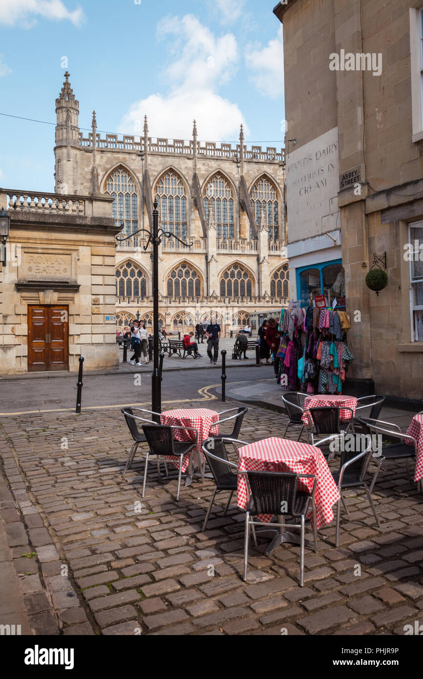 Cafe tables and chairs on a cobbled street, Bath, UK - Stock Image