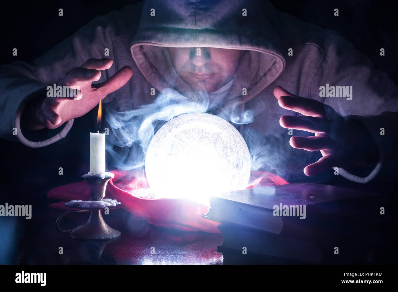 Wizard with hood and lights smoke magic crystal ball on desk with candle in candlestick and old books predicting the future by looking into ball - Stock Image