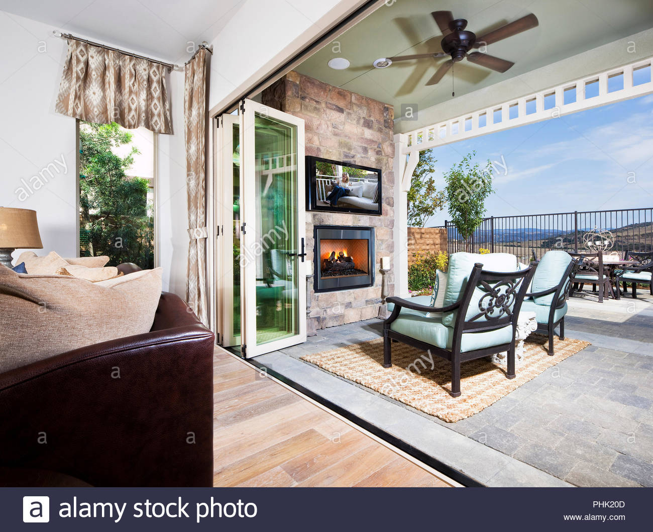 Fireplace and television on patio - Stock Image