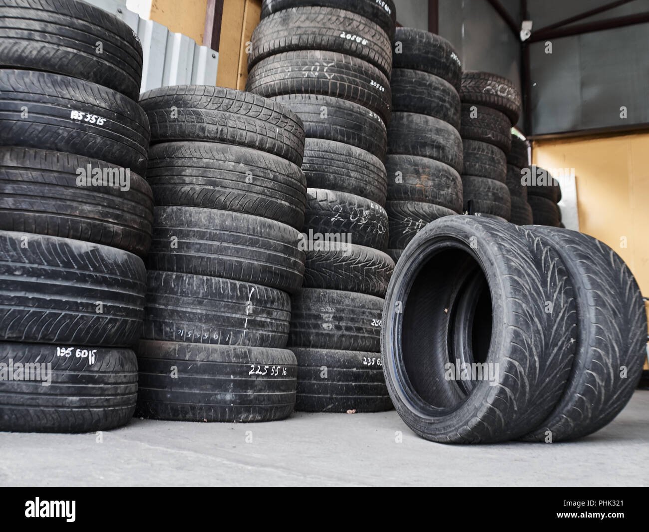 Used car tires stacked in piles at tire fitting service. Wheels for repair shop. Car service concepr - Stock Image
