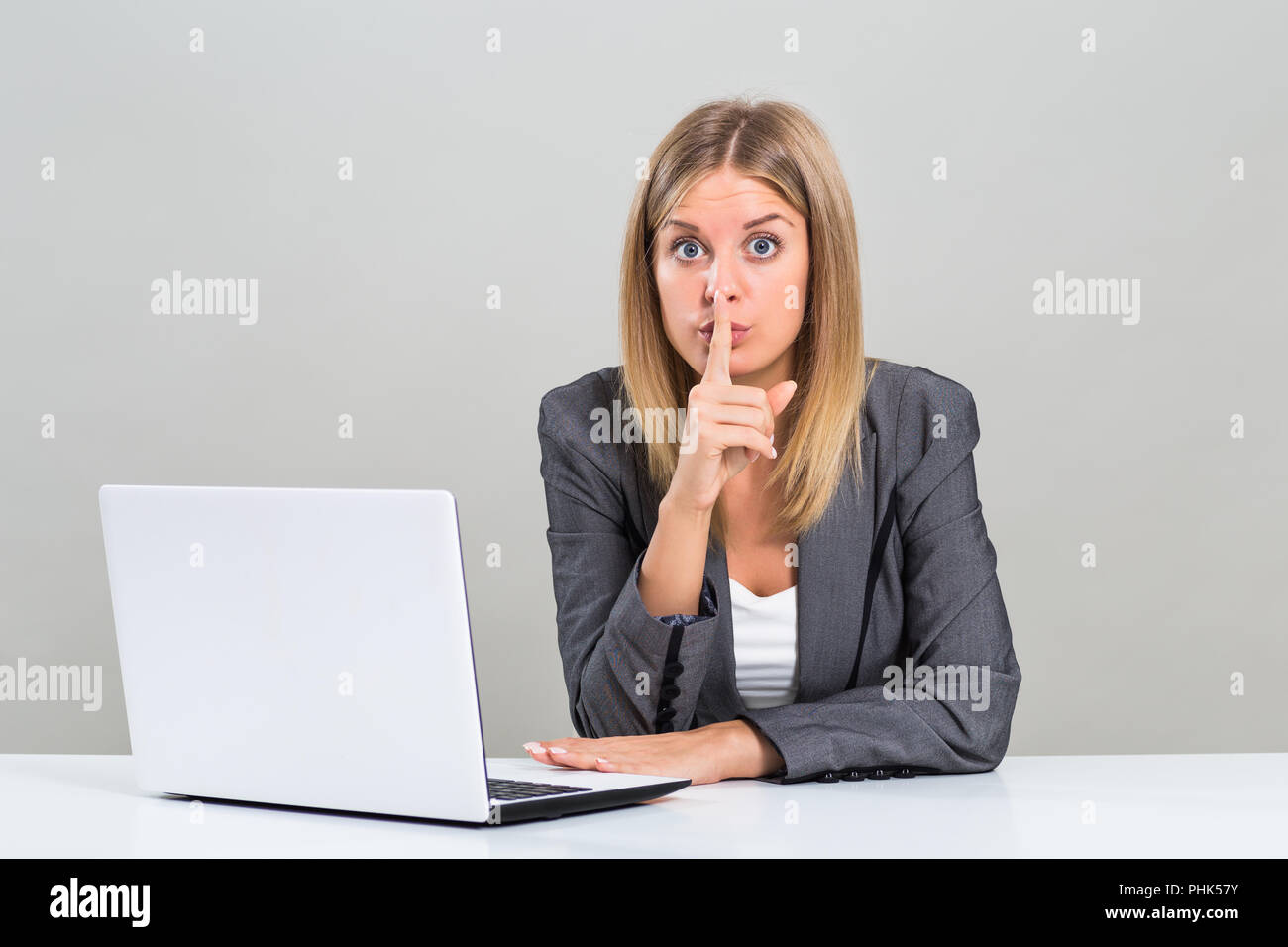 Portrait of beautiful business woman with finger on her lips. - Stock Image