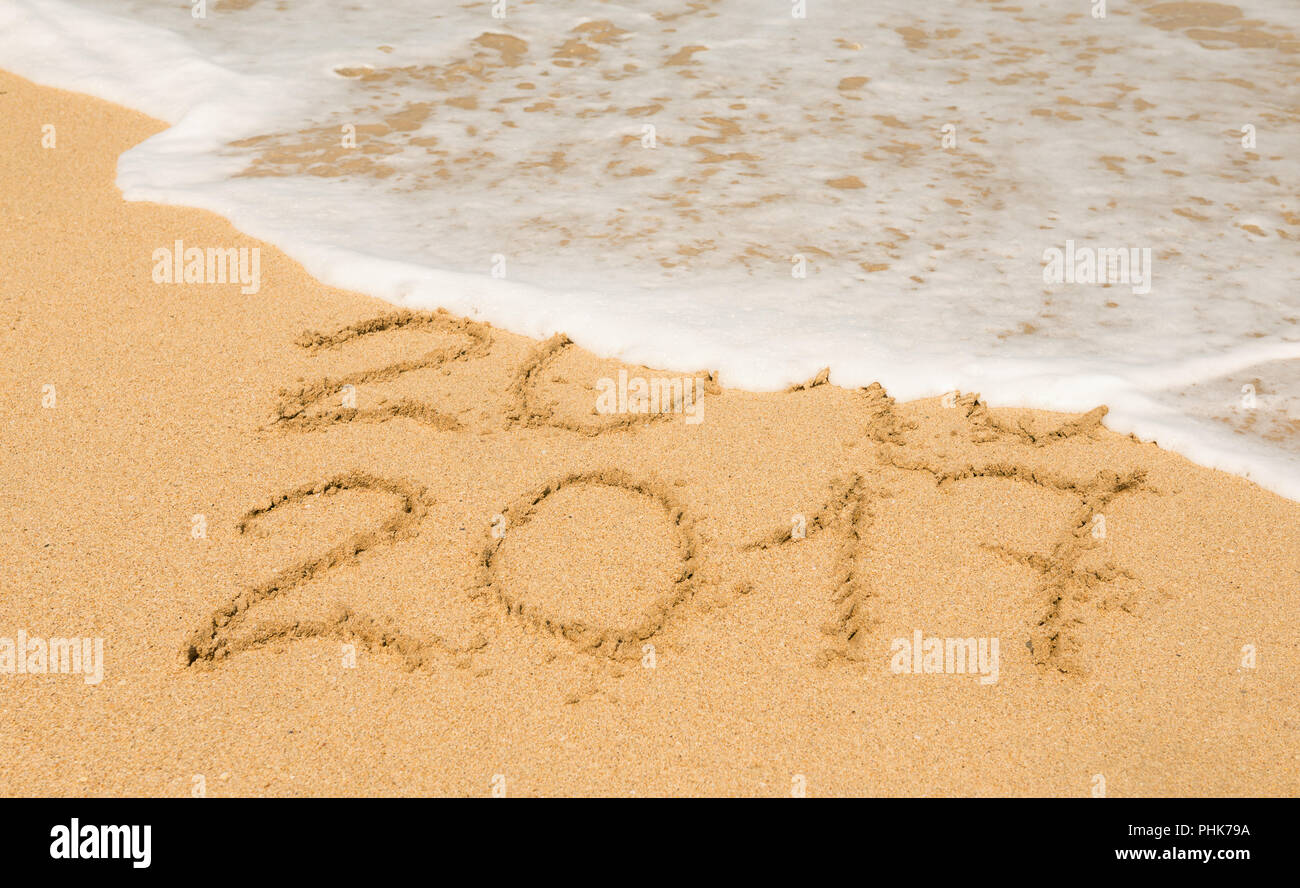 digits  2016 and 2017 on the sand - Stock Image