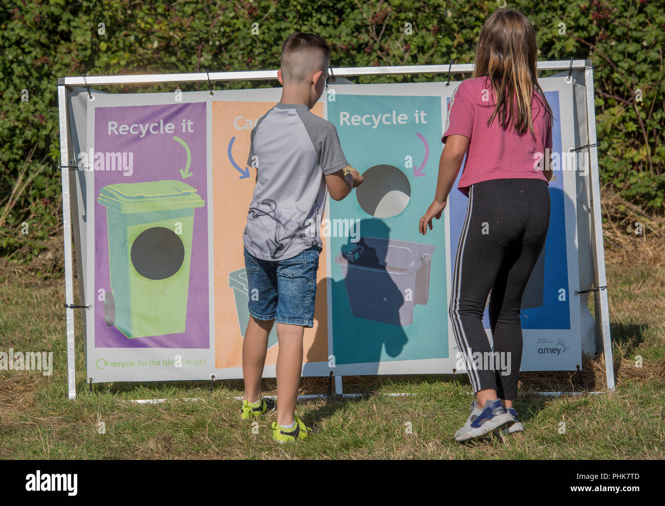 children learning how to recycle different recyclable items by pushing through holes and learning about the environment and sustainability. - Stock Image