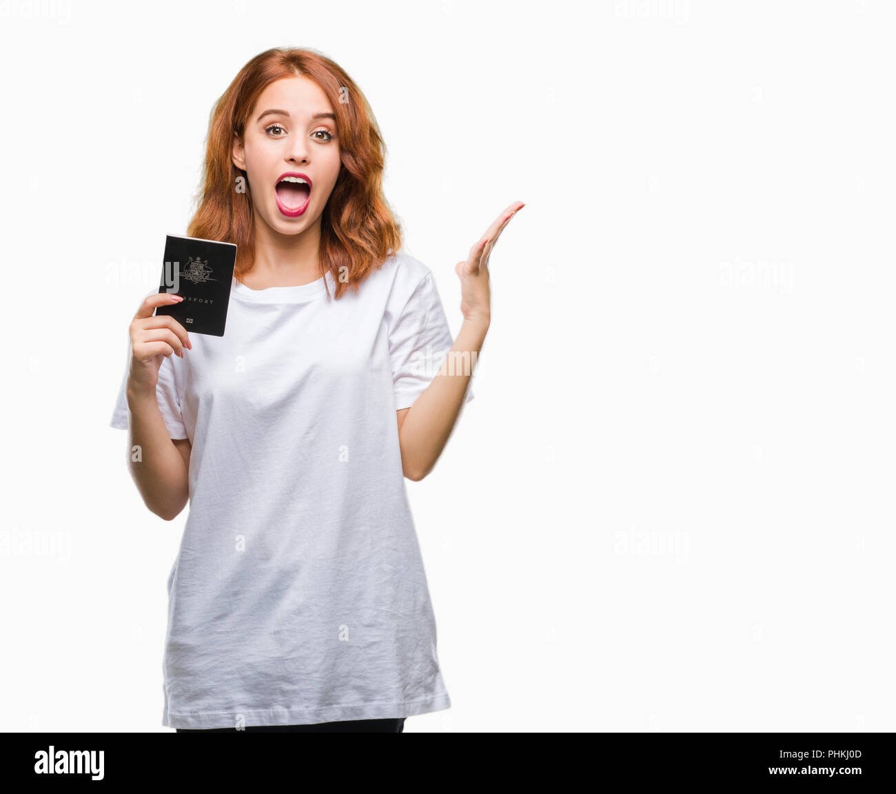 Young beautiful woman holding passport of australia over isolated background very happy and excited, winner expression celebrating victory screaming w - Stock Image