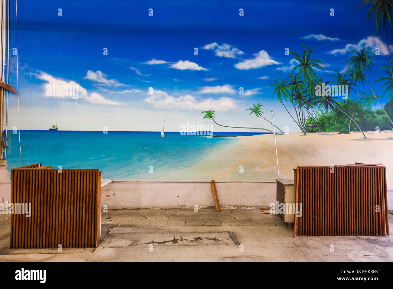Ugly office space with large mural depicting beautiful tropical beach scene. - Stock Image