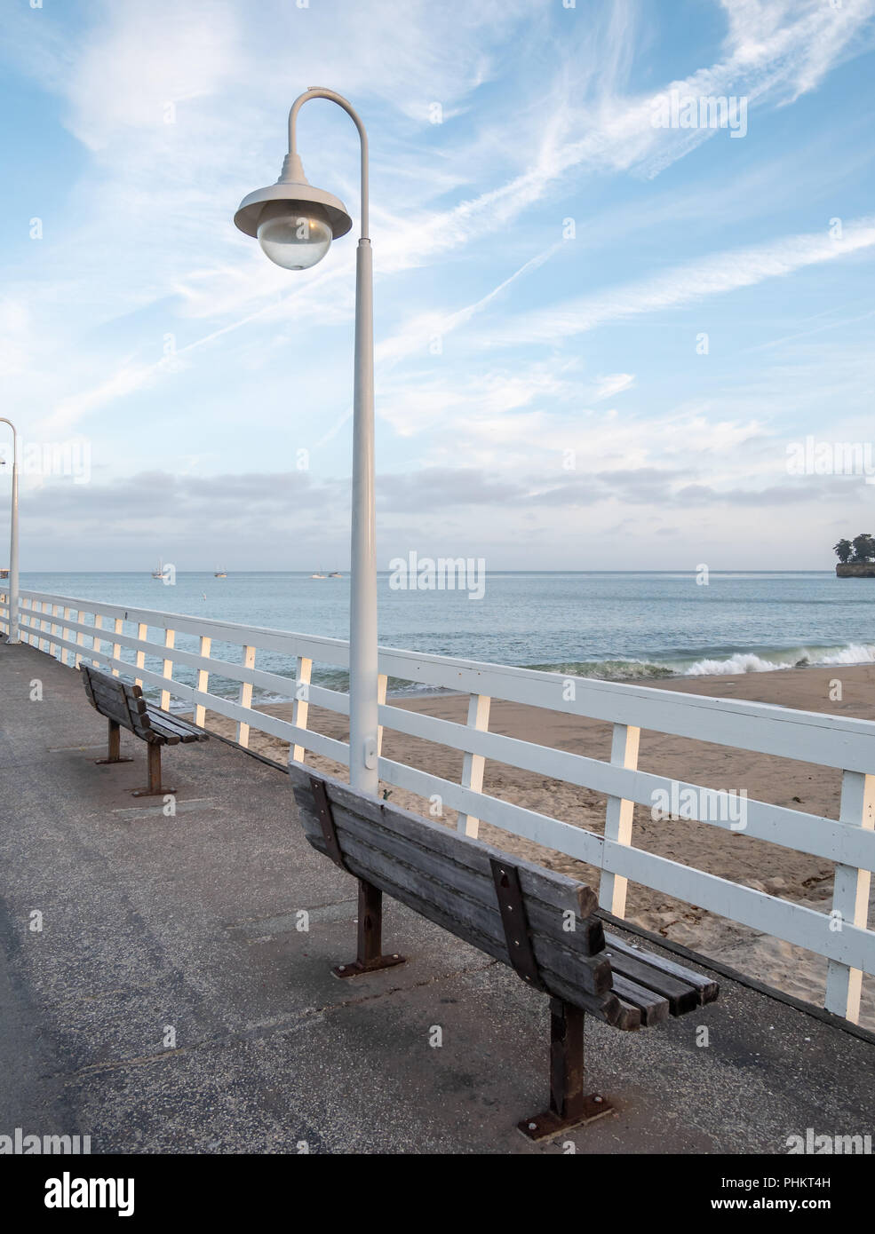 Two Wood Benches On Pier Overlooking the Beach With mostly Sunny Skies - Stock Image