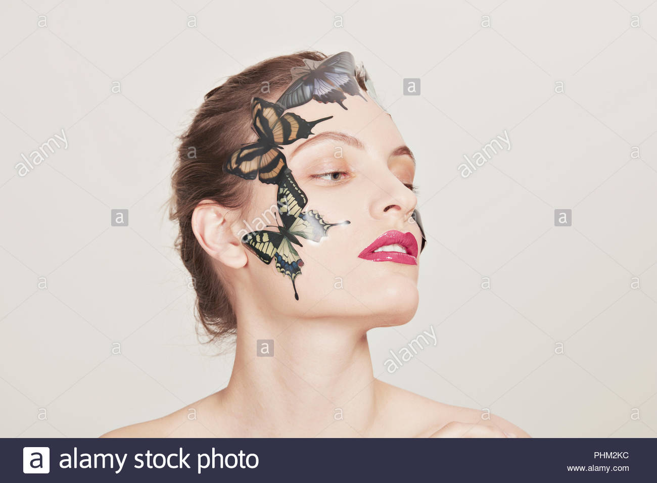 Young woman with butterfly stickers - Stock Image