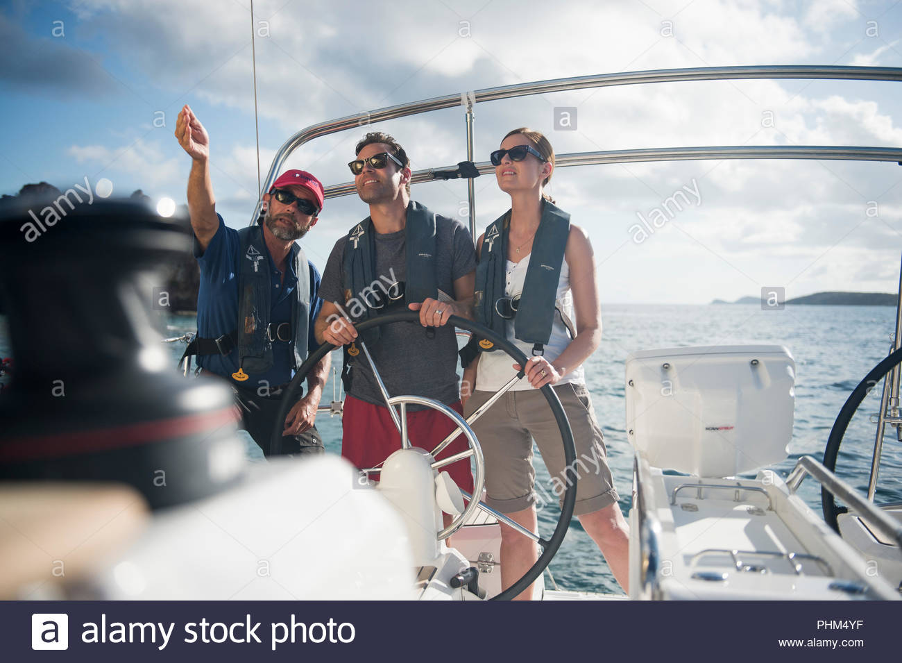 Couple receiving instructions at helm of yacht - Stock Image