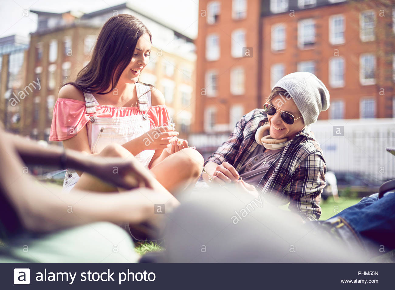 Teenage couple sitting at park - Stock Image