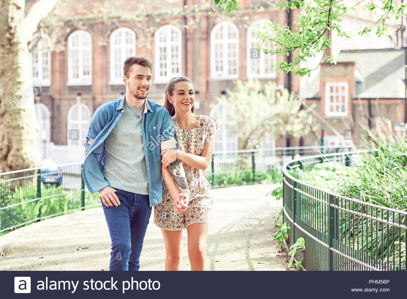 Teenage couple walking in park - Stock Image