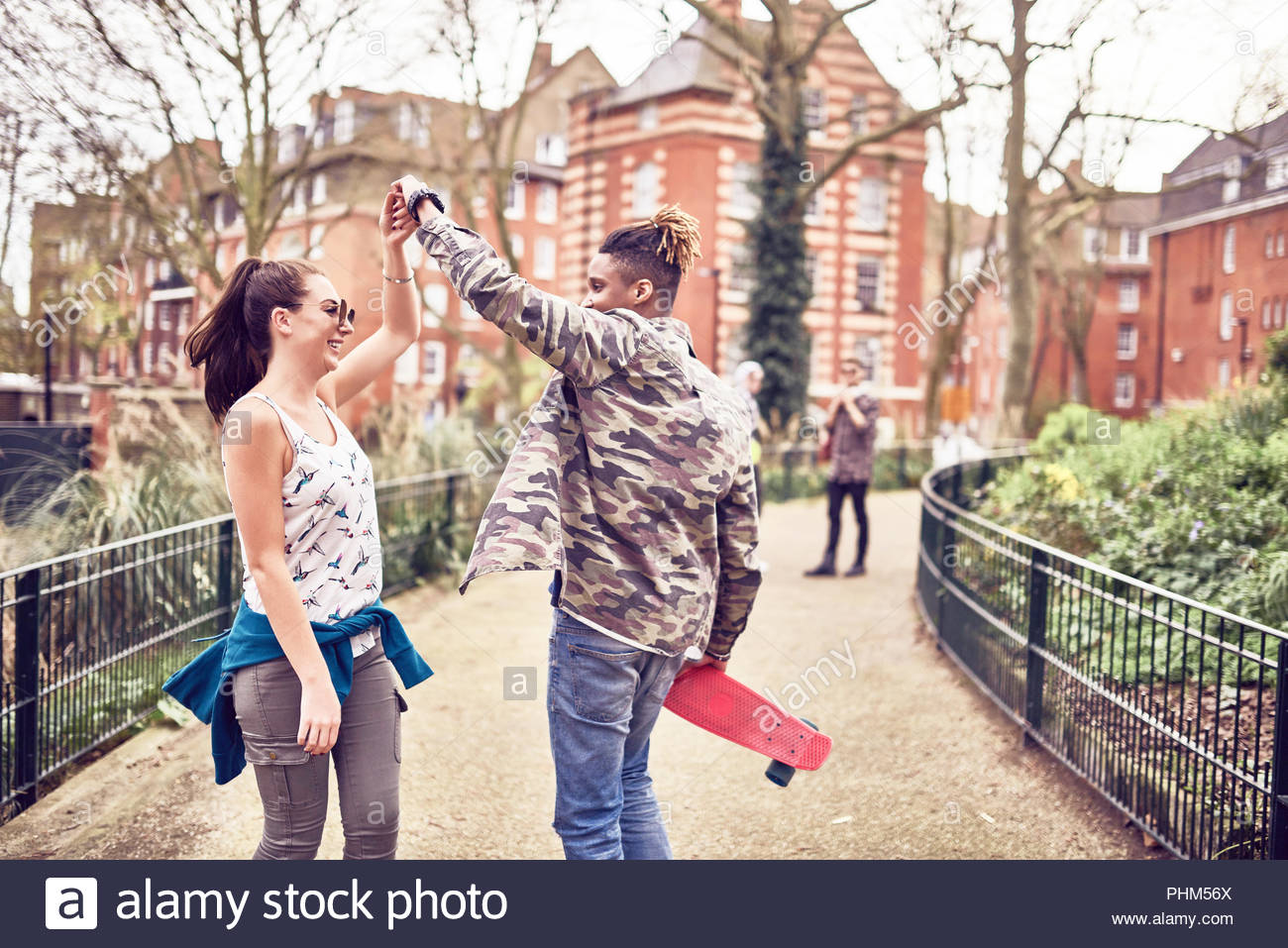 Teenage couple dancing in park - Stock Image