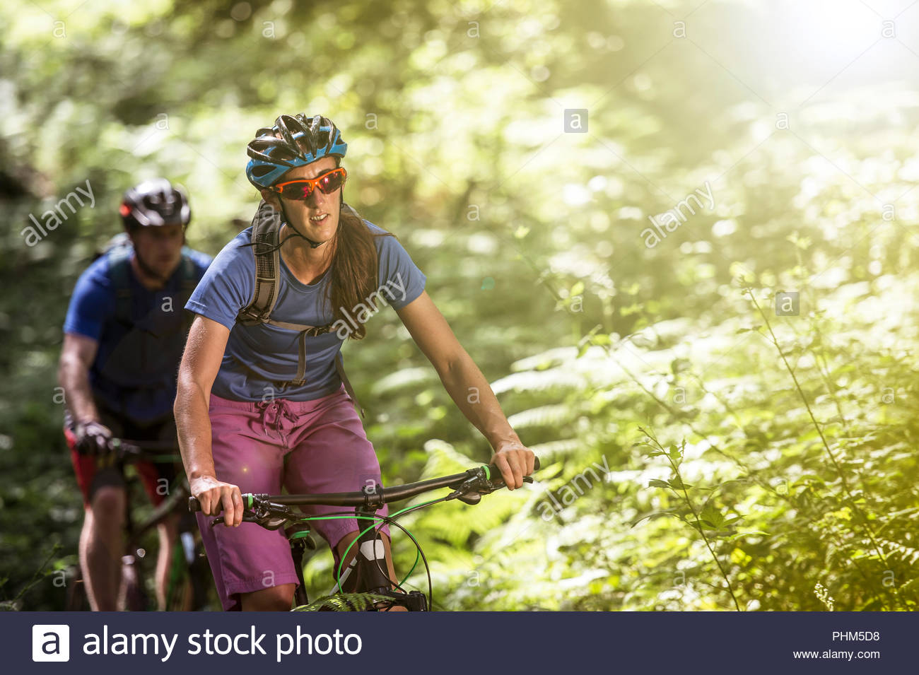 Couple mountain biking in forest - Stock Image