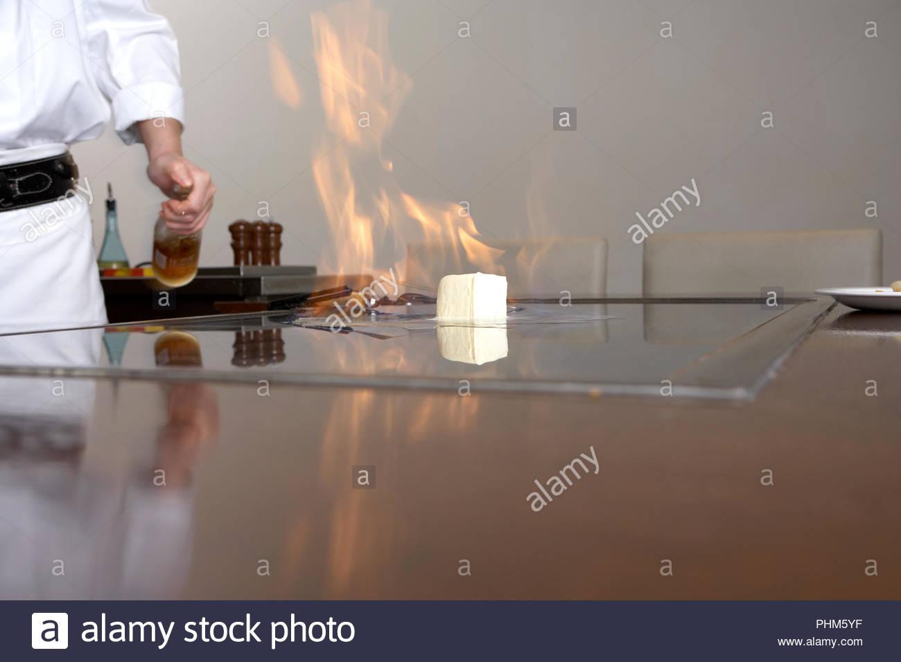 Chef flambeing cheese - Stock Image