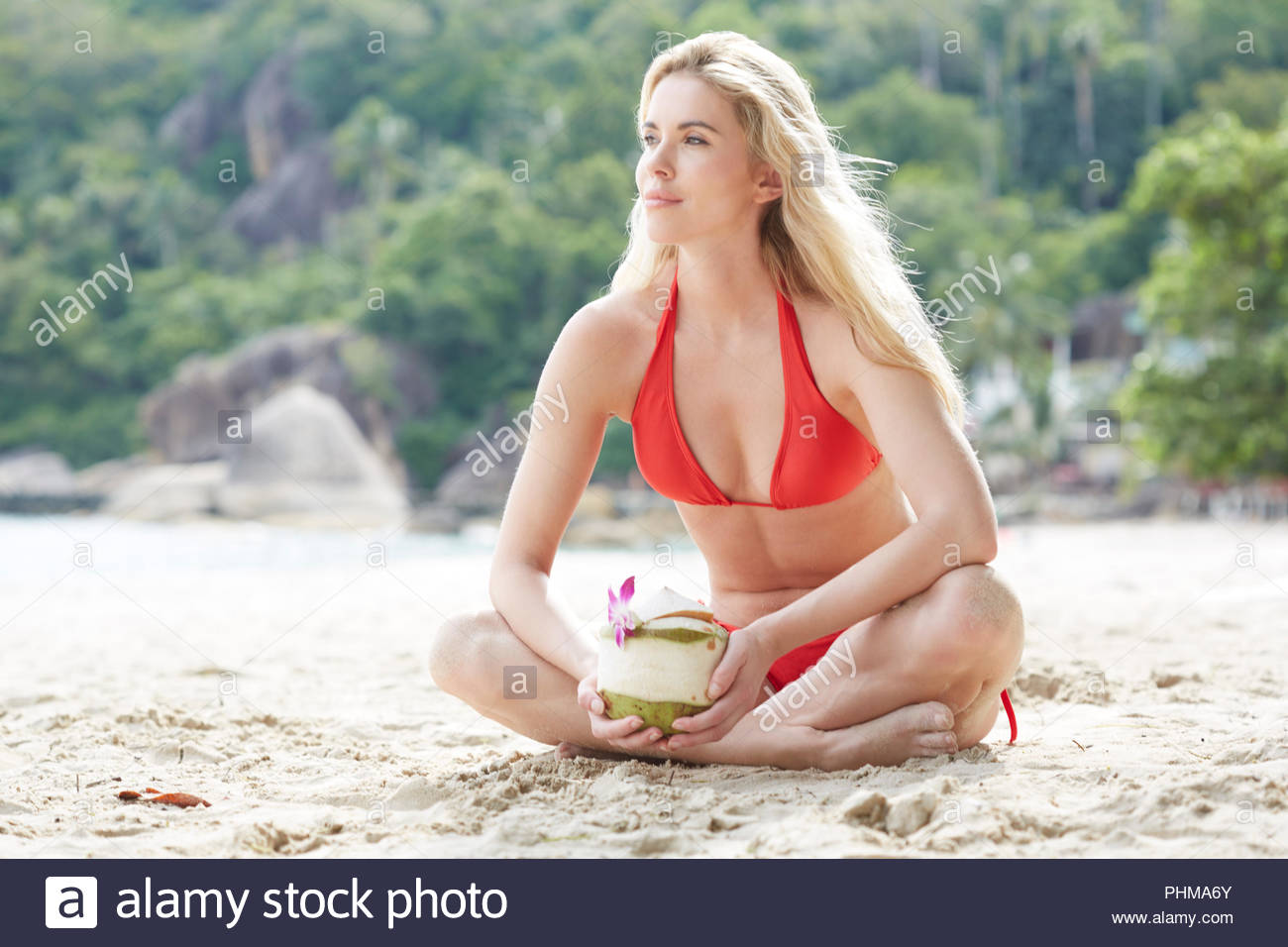 Young woman holding coconut drink on beach Stock Photo