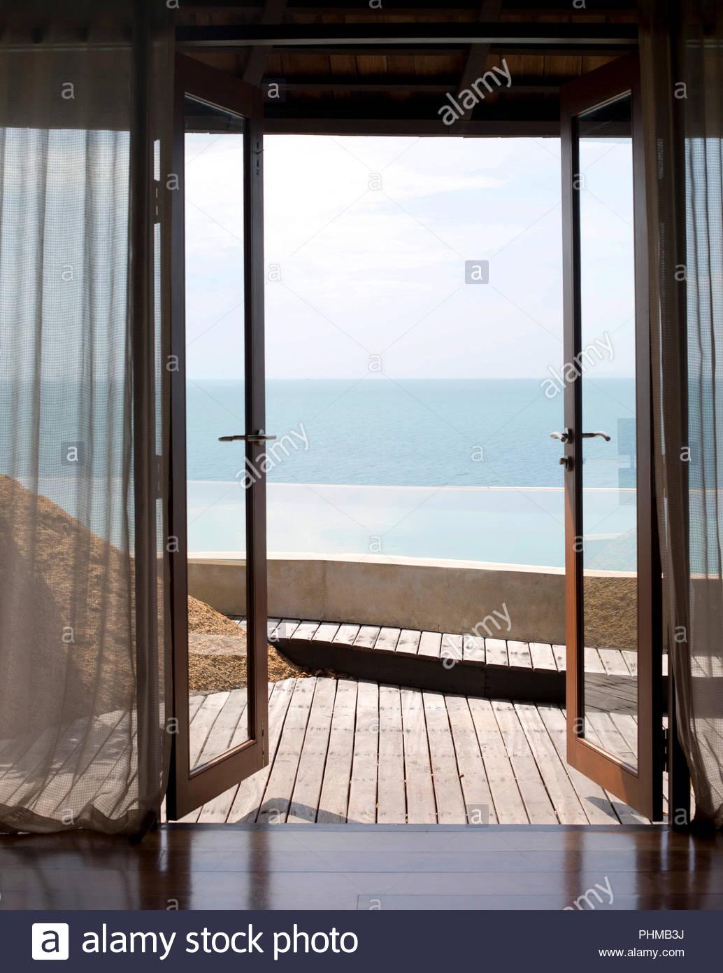 Open glass doors to swimming pool - Stock Image