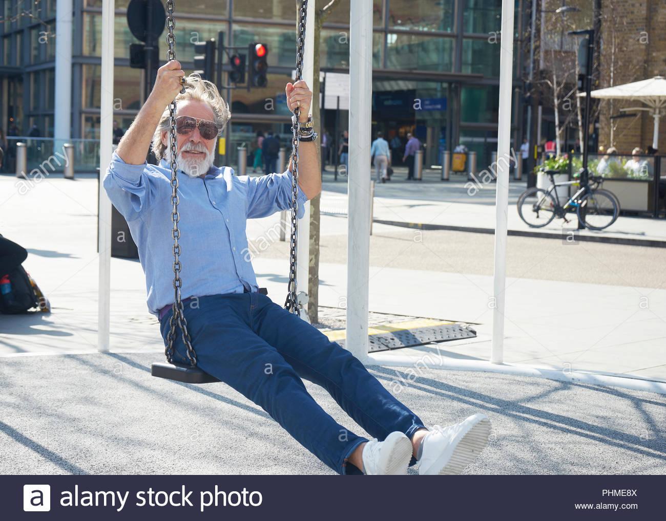 Senior man on swing - Stock Image