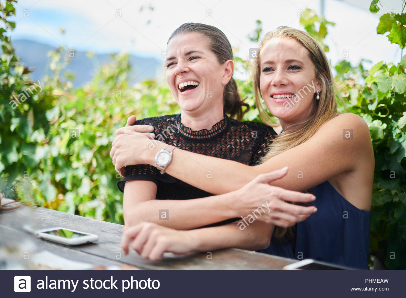 Smiling friends embracing at lunch - Stock Image
