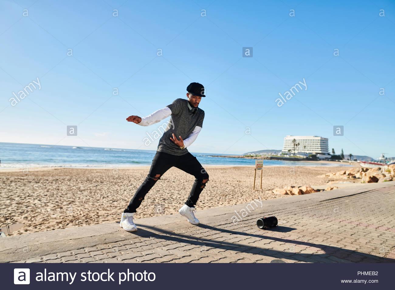 Young man break dancing by beach - Stock Image