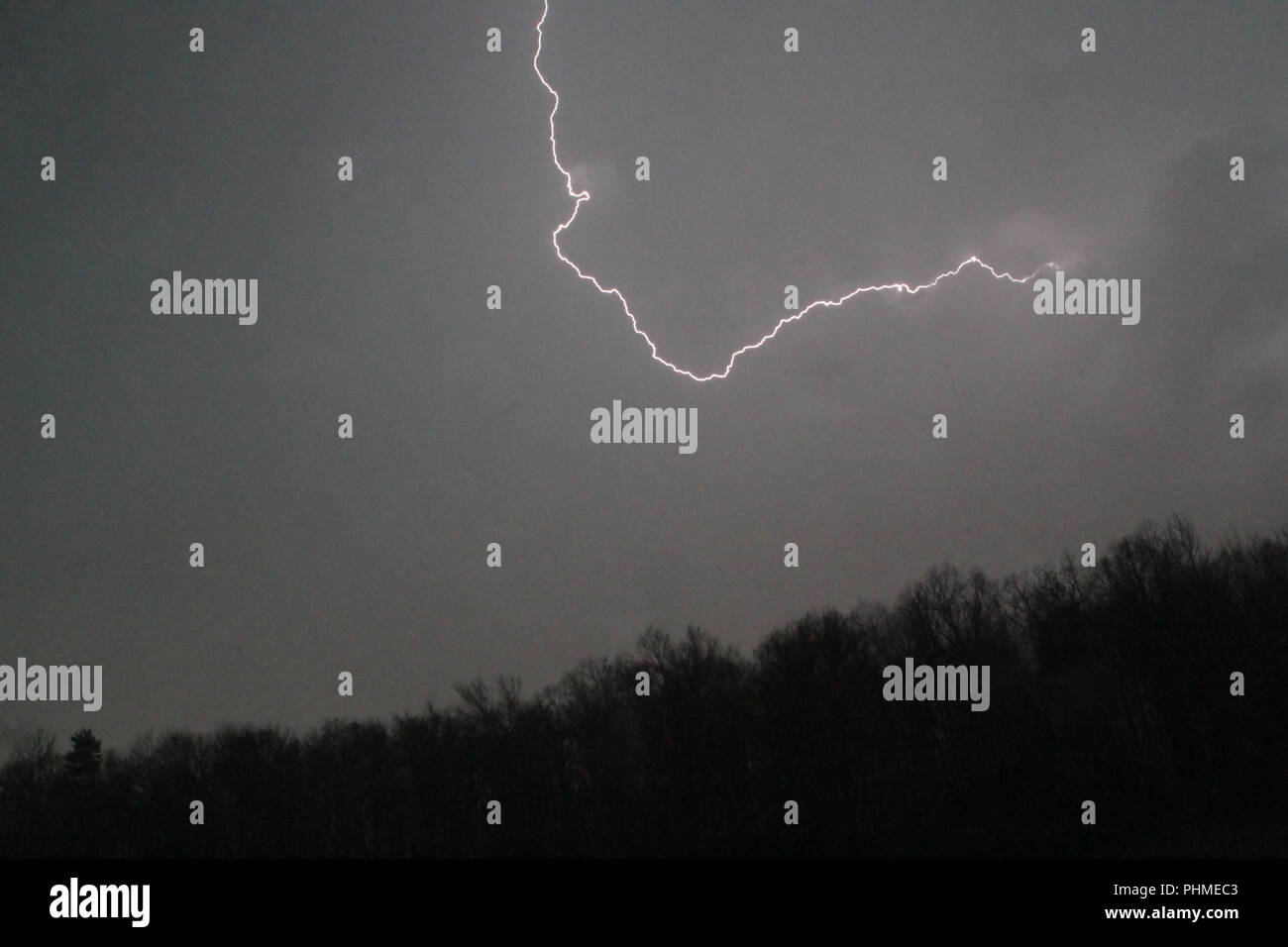 lightning bolt in sky above mountain Stock Photo