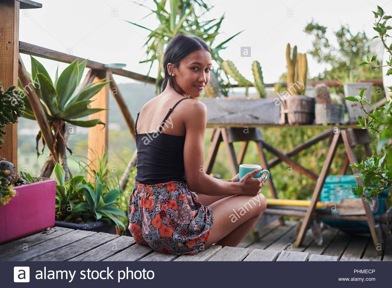 Young woman sitting on balcony with coffee cup - Stock Image