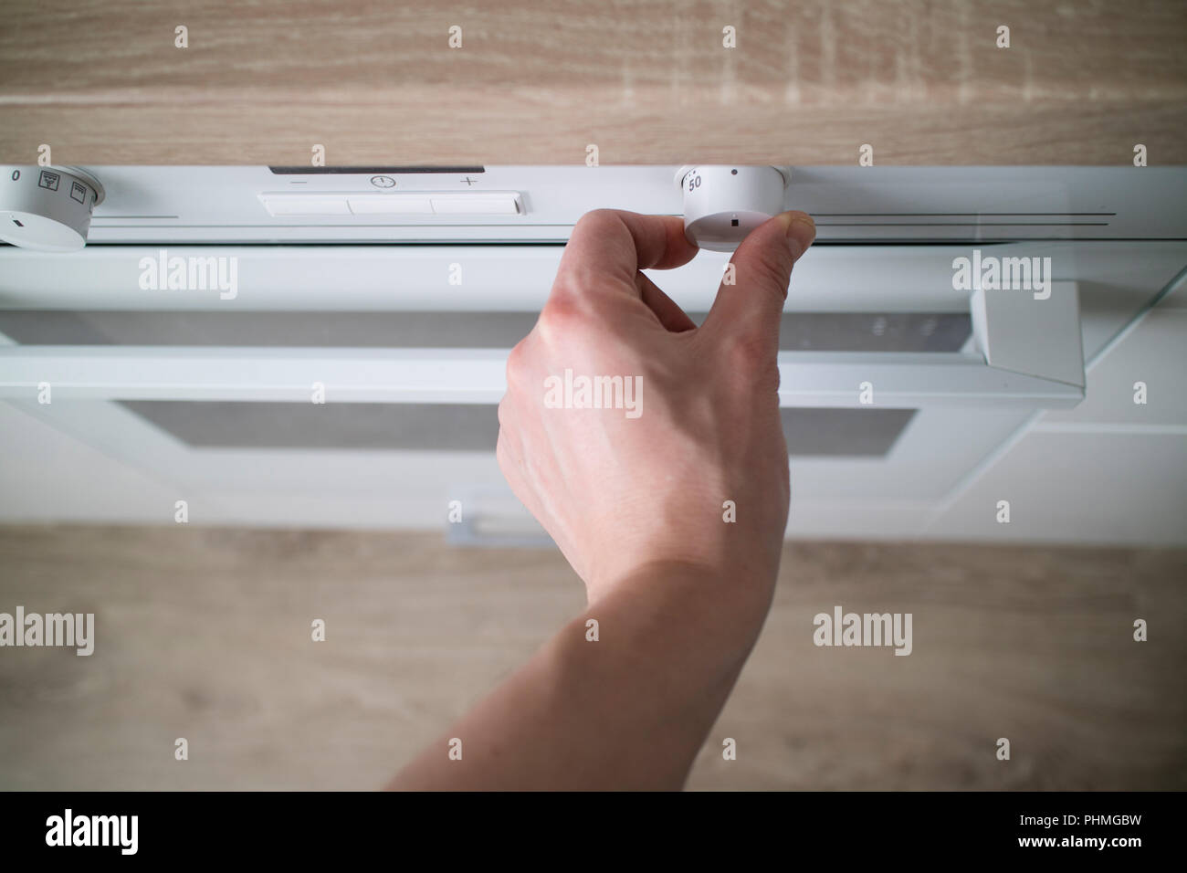 man hand setting temperature control on oven - Stock Image