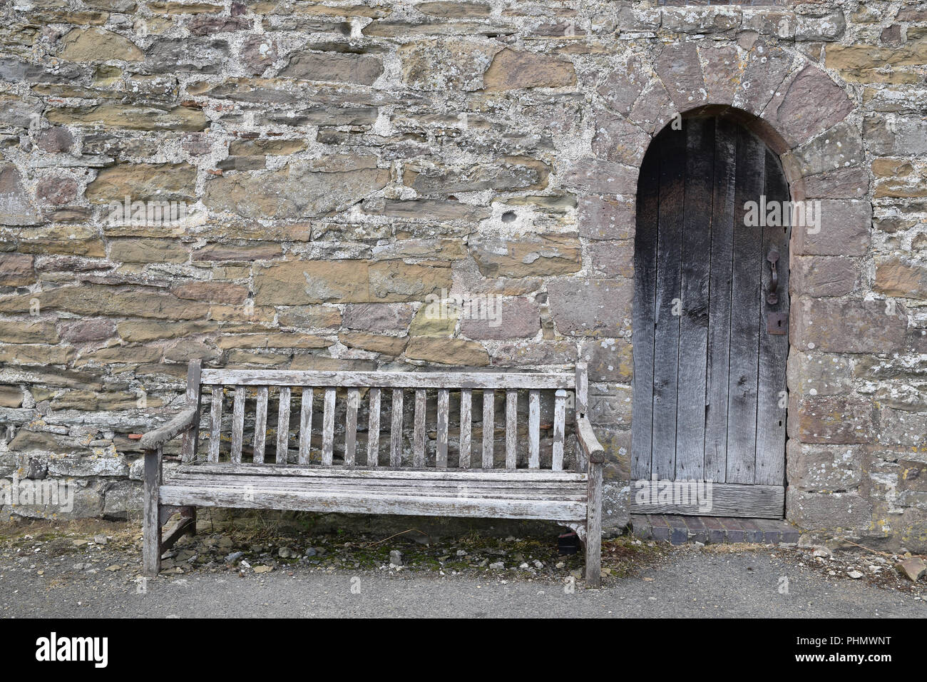 Weathered old bench against the stonewall of a church with an arched wooden door. Relaxing spot to sit contemplation - Stock Image