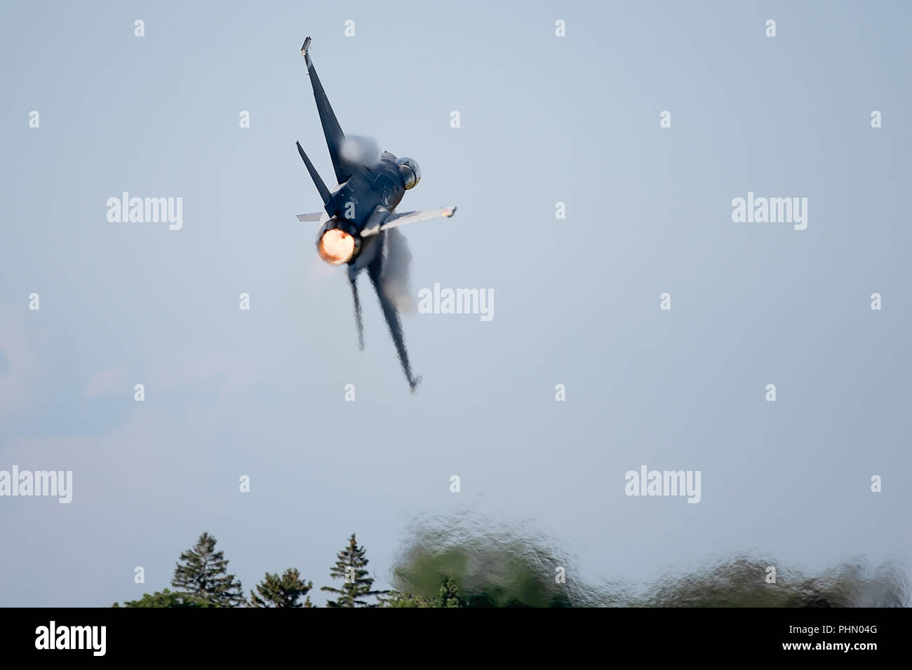 Oshkosh, WI - 28 July 2018:  A F-16 flying falcon starting to turn with full afterburner and contrails starting to come over the wings at the EAA airs - Stock Image