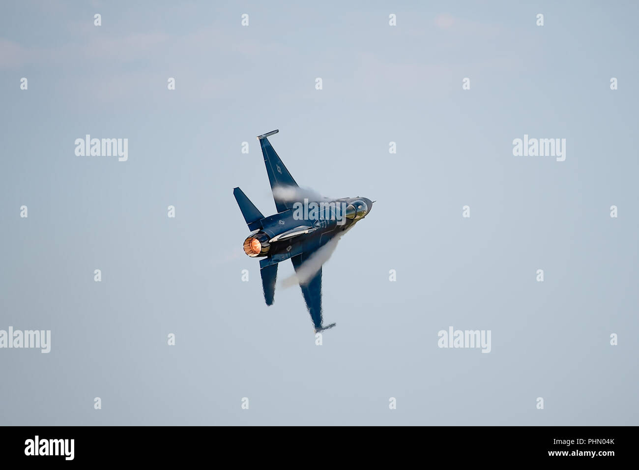 oshkosh, WI - 28 July 2018:  A F-16 flying falcon starting to turn with full afterburner and contrails starting to come over the wings at the EAA airs Stock Photo