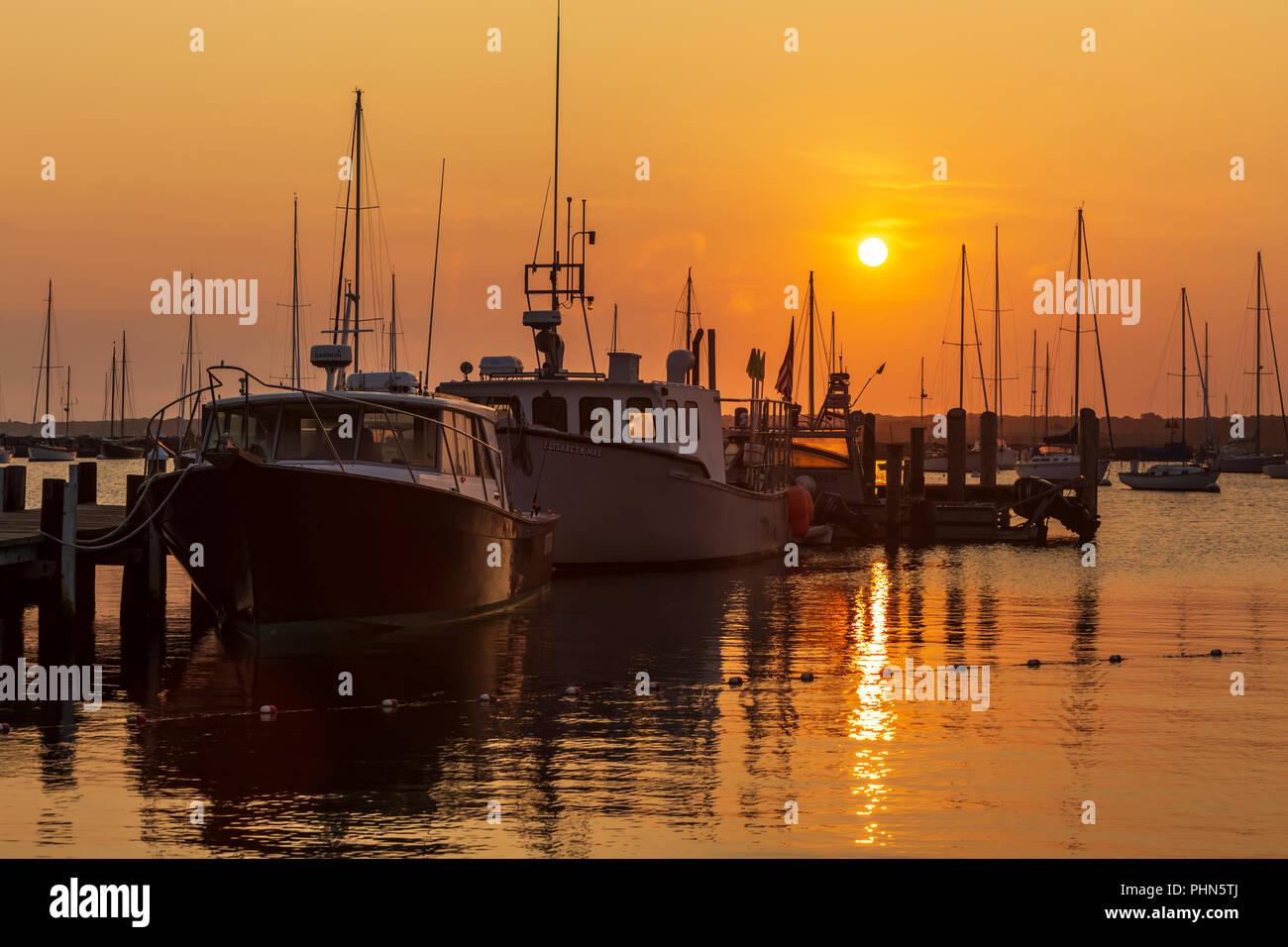 The sun rises over fishing boats and pleasure craft in Vineyard Haven Harbor in Tisbury, Massachusetts on Martha's Vineyard. Stock Photo