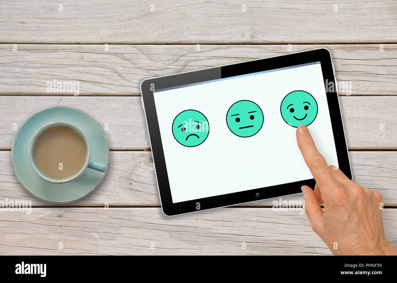 Customer satisfaction feedback survey questionnaire with hand choosing smiley - Stock Image