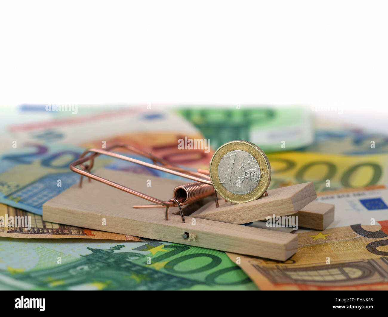 close up of euro coin in mousetrap as bait on banknotes with copy space. concept of debt - Stock Image