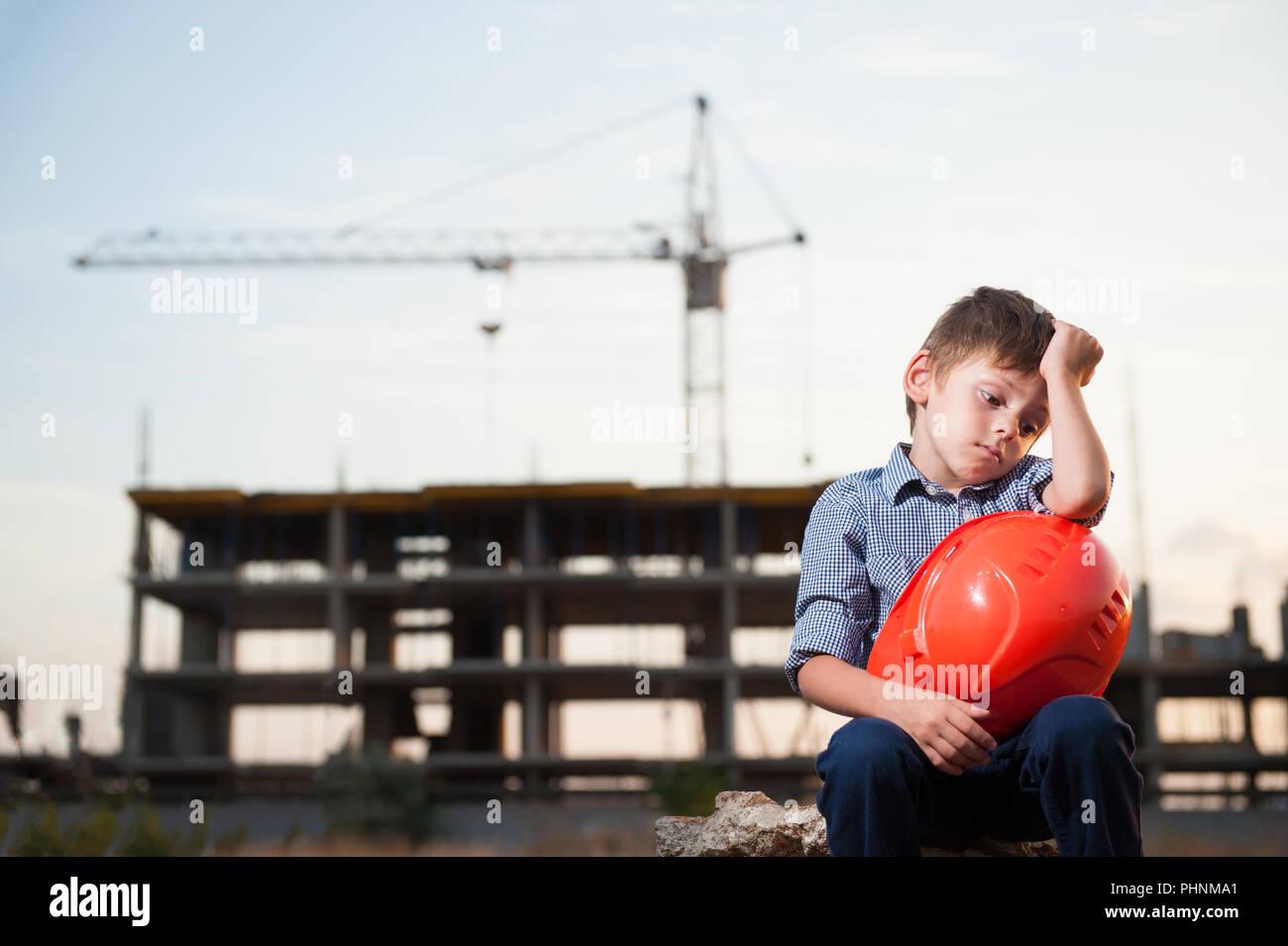 cute upset little boy sitting near building site with orange helmet in hands - Stock Image