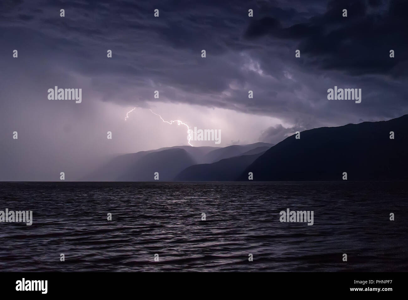 Amazing view with a flash of lightning in dark blue clouds during a thunderstorm over a lake in the mountains - Stock Image