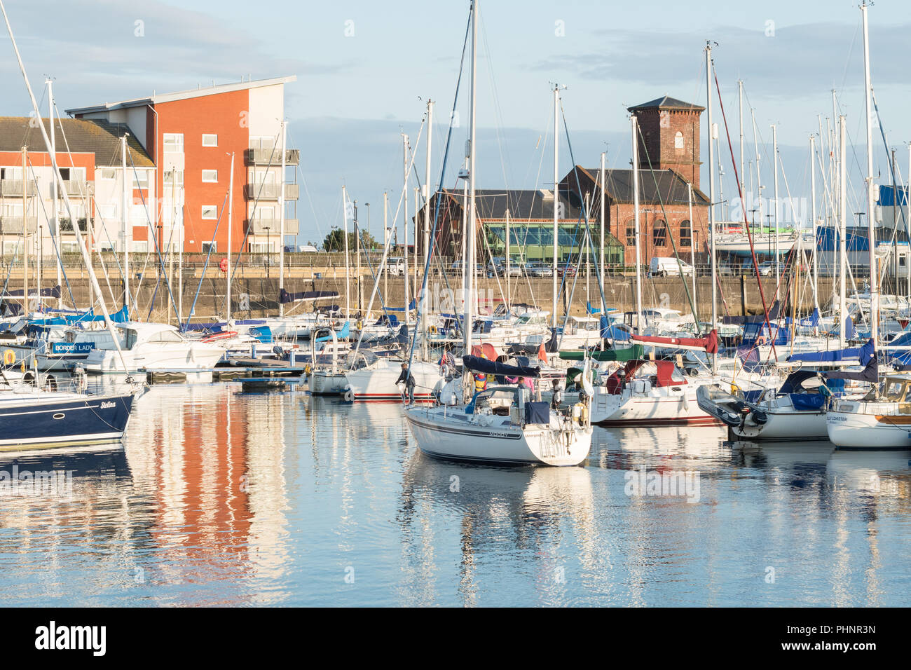Yacht arriving at Clyde Marina and old Power House Adrossan Harbour, now Cecchinis Italian Bar Bistro and Restaurant, Ardrossan, Scotland, UK - Stock Image