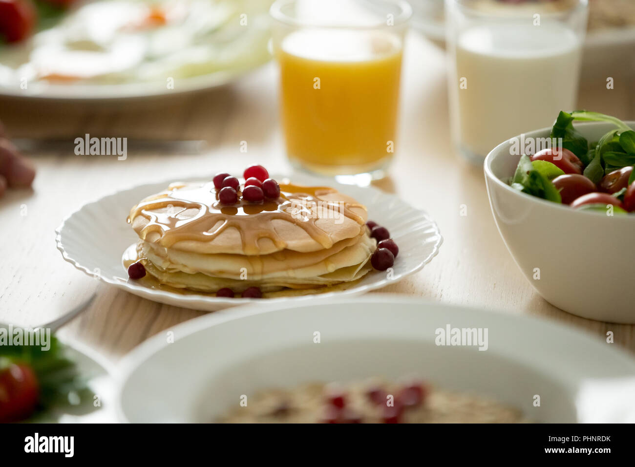 Close up of tasty pancakes served with syrup and berries - Stock Image