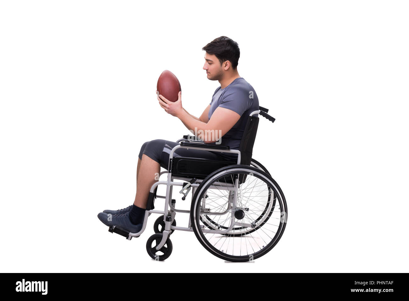 Football player recovering from injury on wheelchair - Stock Image