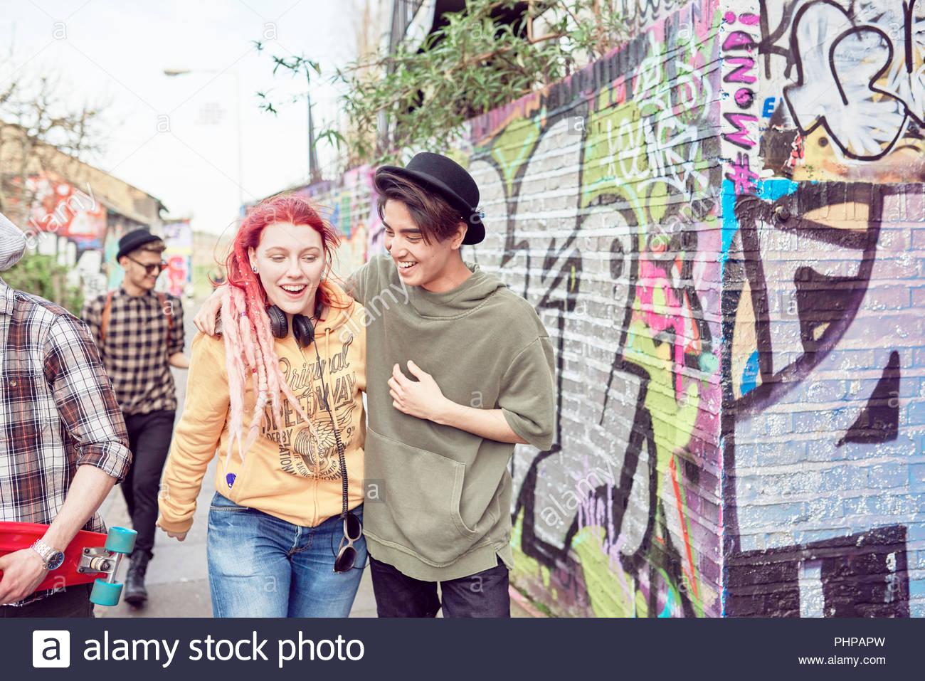 Teenage couple walking along street together - Stock Image