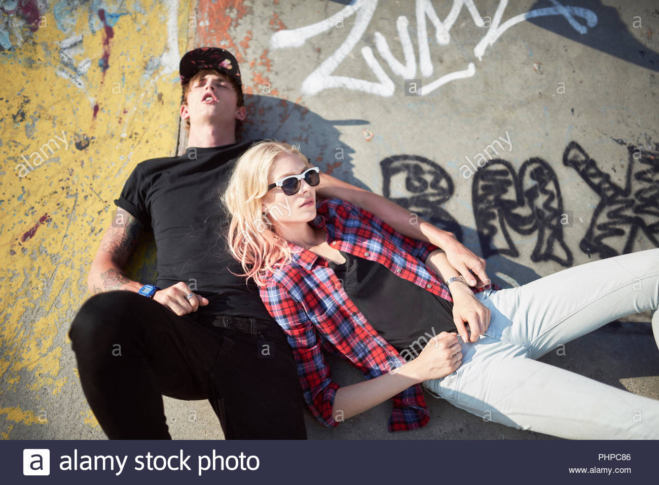 Teenage couple lying down at skatepark - Stock Image
