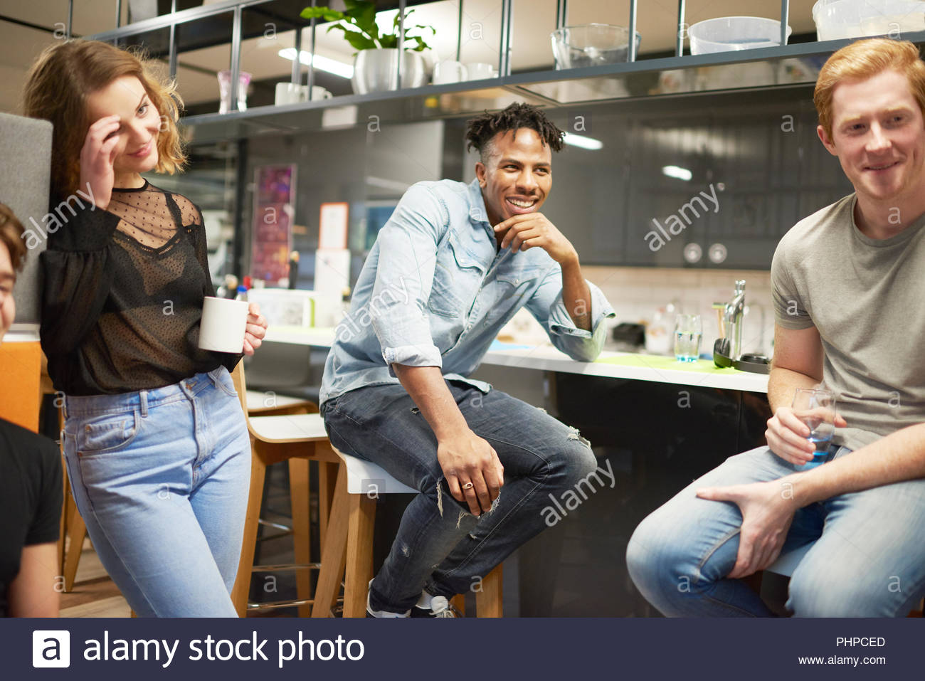 Colleagues talking in office kitchen - Stock Image