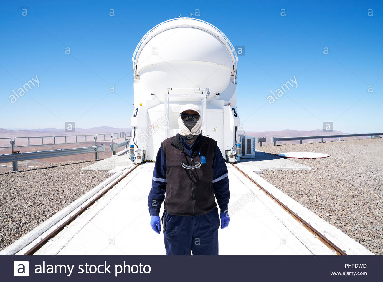 Masked scientist by telescope at Paranal Observatory - Stock Image
