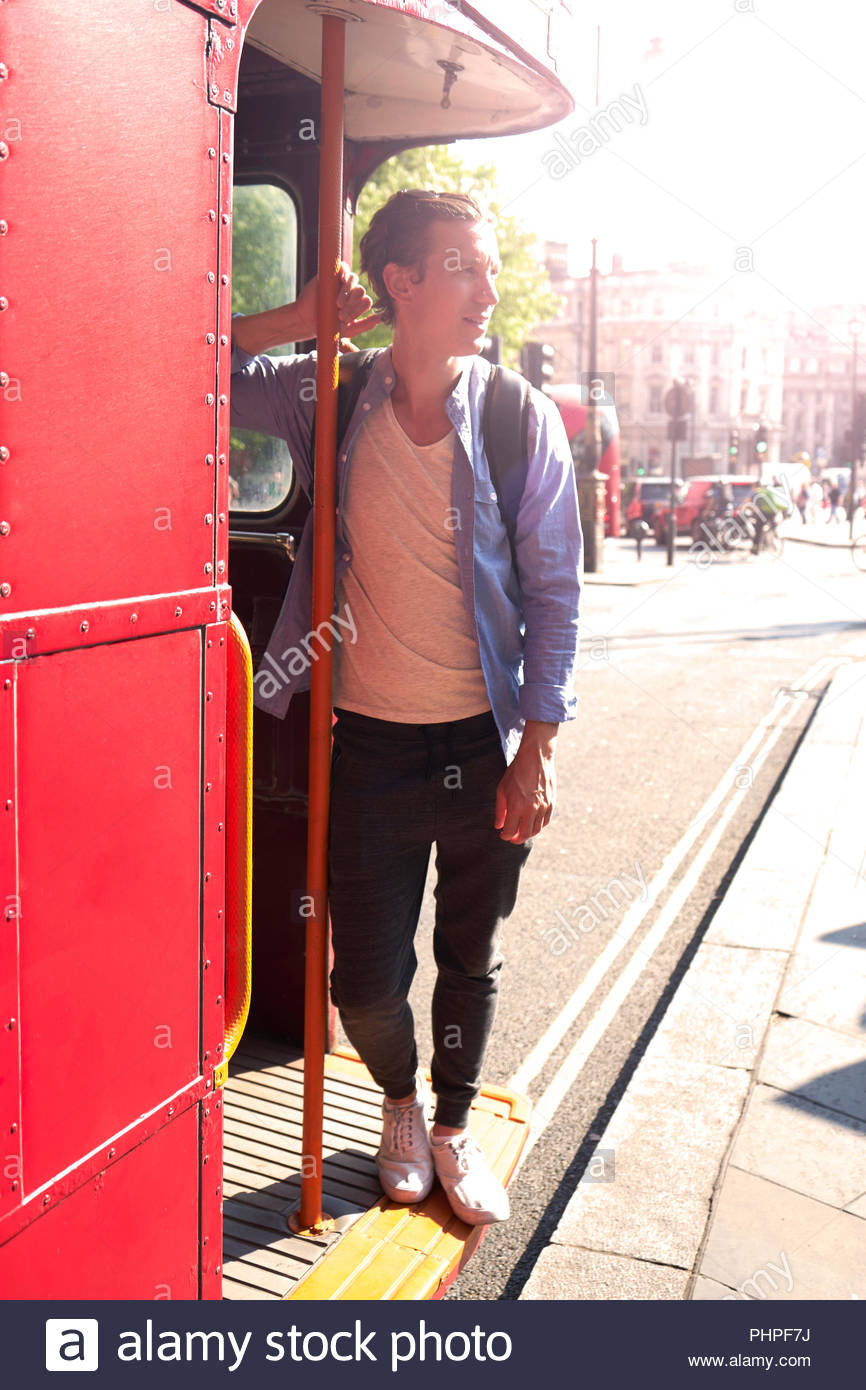 Mid adult man standing on bus - Stock Image
