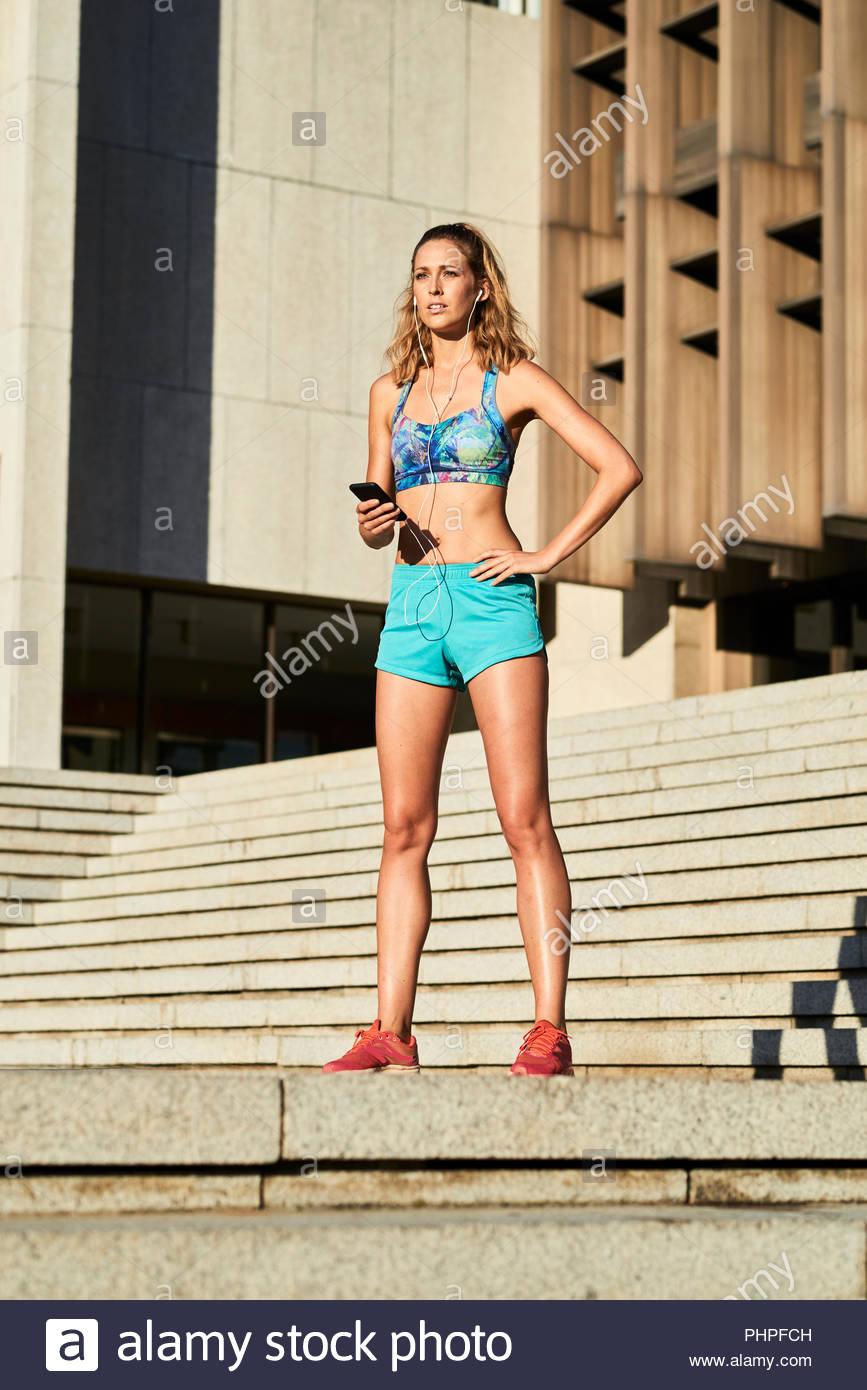 Woman wearing sportswear listening to music - Stock Image
