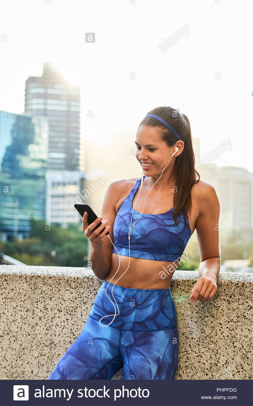 Woman wearing sports bra listening to music - Stock Image
