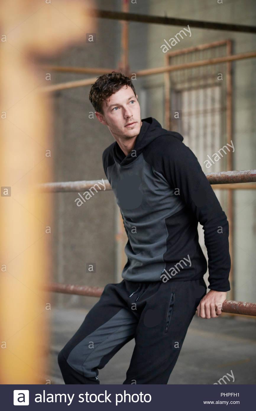 Man wearing hoodie leaning on railing - Stock Image