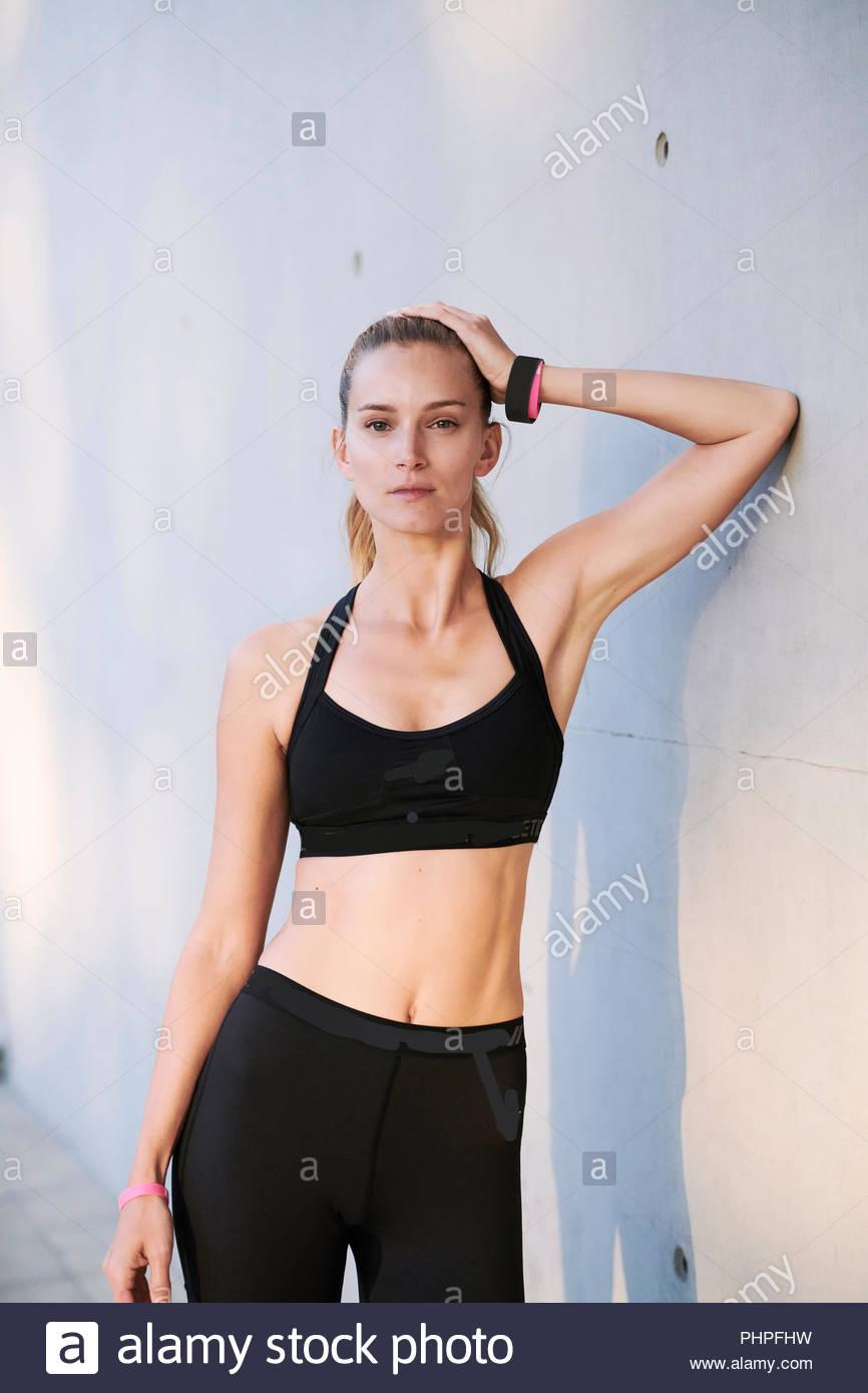 Woman wearing sports bra leaning on wall - Stock Image