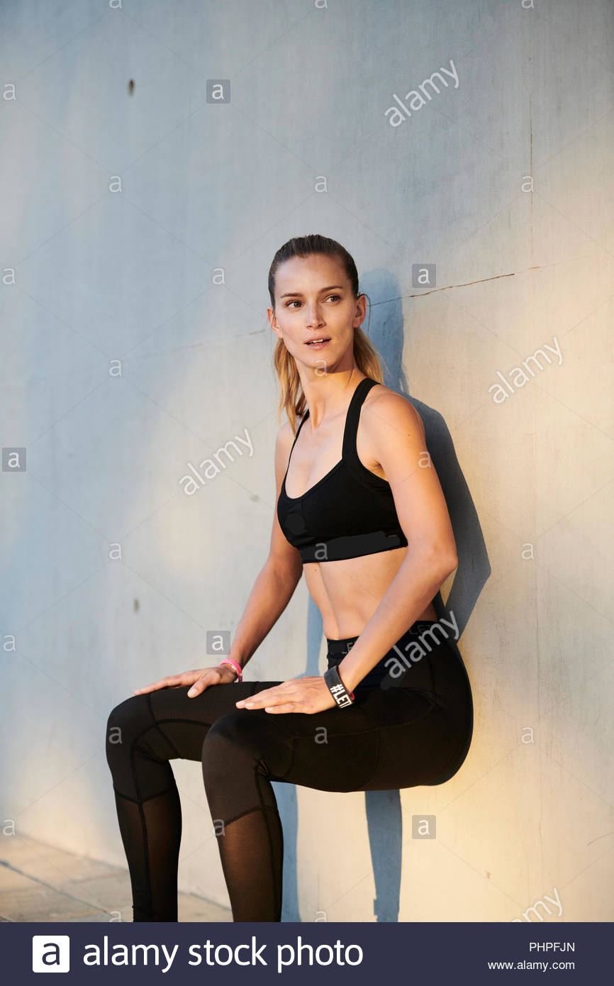 Woman sitting on wall - Stock Image