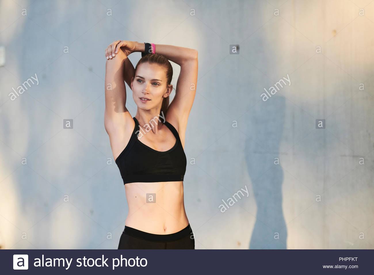 Woman wearing sports bra stretching - Stock Image