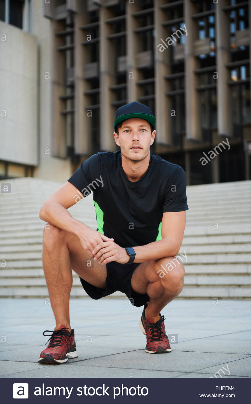 Man wearing sportswear crouching - Stock Image